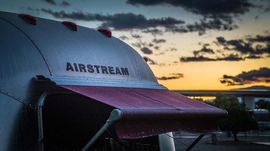 Airstream travel trailer with awning at sunset.