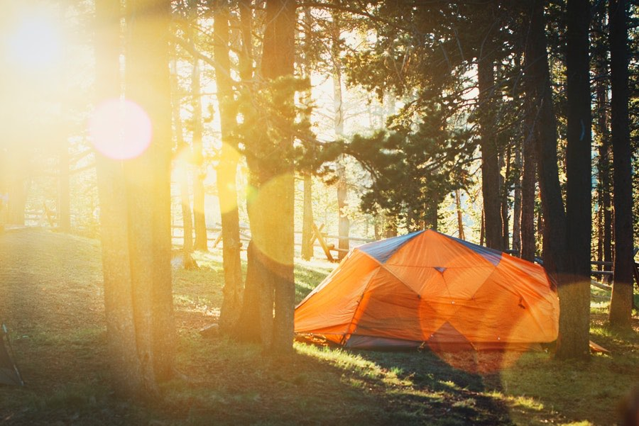 large orange camping tent in the woods