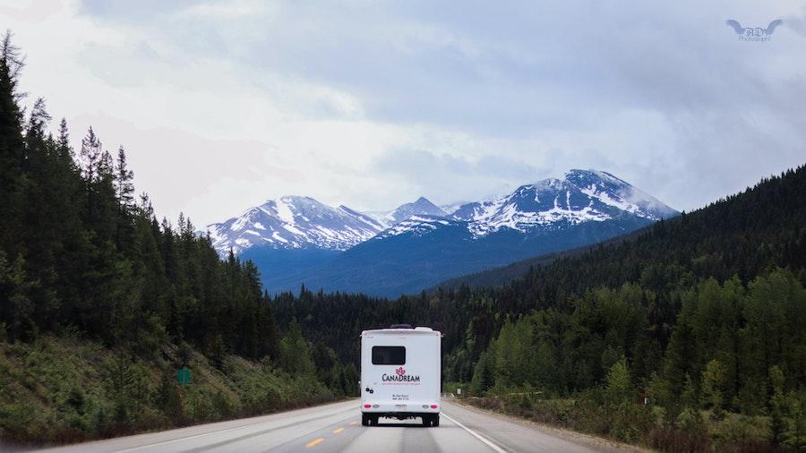 white RV driving through mountain road in British Columbia