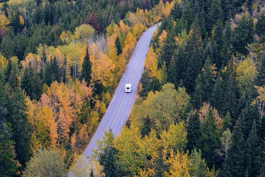 RV driving down two lane road in woods with trees changing autumn colors