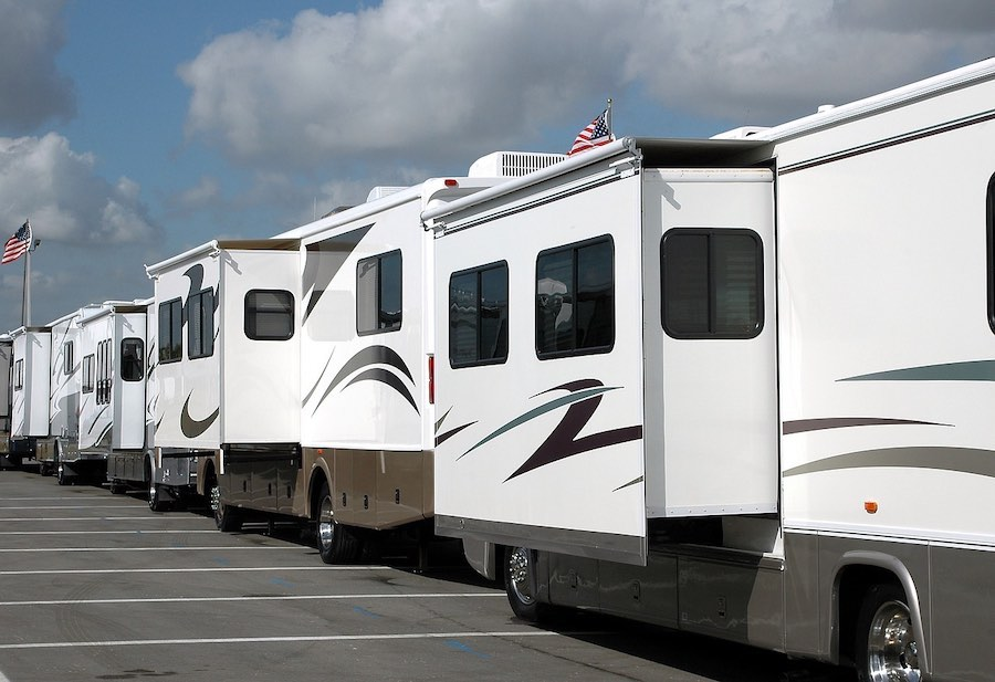 row rvs camping in parking lot at store
