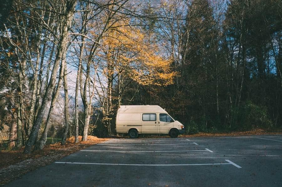 white camper van boondocking in parking lot near forest
