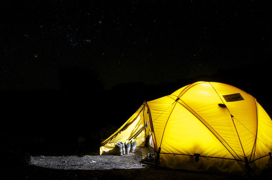 yellow camping tent illuminated from the inside at night
