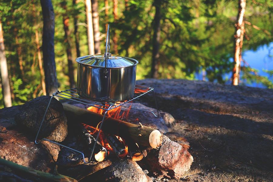 pot warming up on campfire while camping
