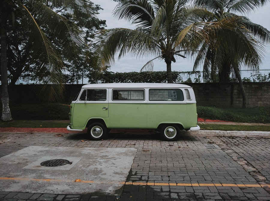 Green camper van parked in front of palm trees on street.